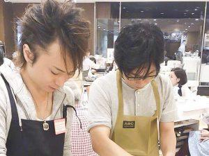 料理学校に通って料理を習う男性2人の画像